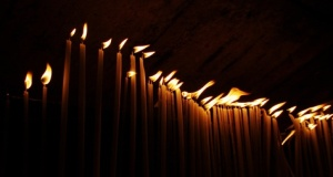 Many candles in a row in dark church