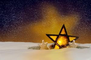 Leuchtender Weihnachtsstern bei Nacht im Schnee
